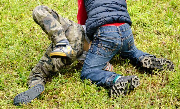 Kaverinsa isän haukkujen kohteeksi joutunut poika otti 10-vuotiaasta kiinni ja painoi hänet maahan yhden pojista alkaessa potkia uhria. Kuvituskuva.