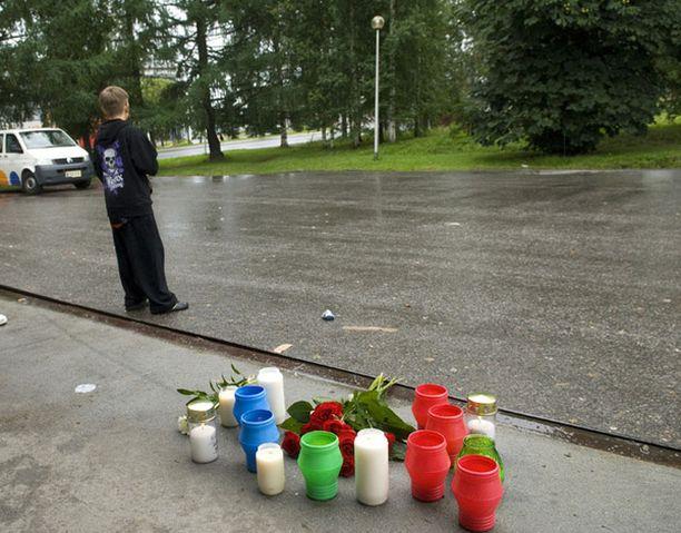 Kynttilät paloivat puiston laidalla surmatun tytön muistoksi.