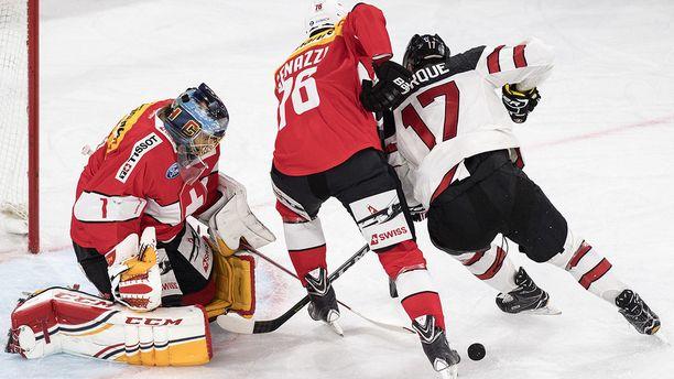 Sveitsin maalivahti Jonas Hiller ja puolustaja Joel Genazzi torjuvat Kanadan Rene Bourquen lähentelyt.