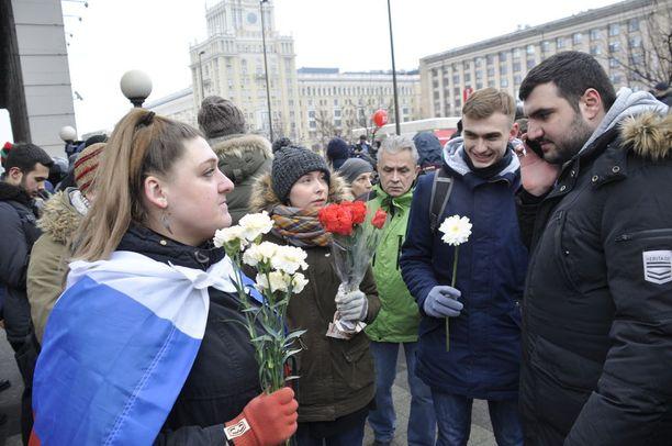 Meillä on kukkia, koska haluamme näyttää poliiseille, että olemme rauhaisissa aikeissa. Poliisitkin joutuvat olemaan ulkona kylmässä, se ei ole heillekään mukavaa, sanovat Larissa (vas.), Nastja, Dmitri ja David