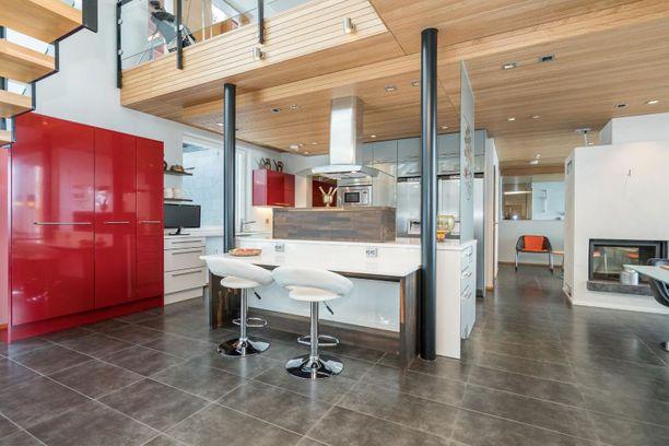 Saarekekeittiö baarijakkaroineen, takka ja korkea olohuone muodostavat yhdessä laadukkaan kokonaisuuden.