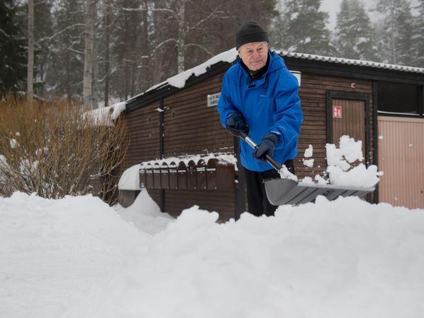 Tampereen kaupungin vanhusneuvoston jäsen Lauri Lepistö lumitöissä pihallaan.