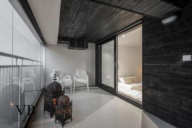 Sisäänvedetty, musta parveke kerrostalossa keskellä Helsinkiä on harvinaisuus. Tila on sisustettu kahdella taljoin vuoratulla tuolilla.