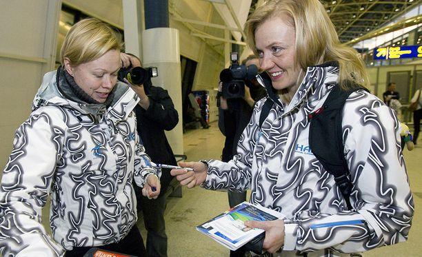 Virpi Kuitunen sai kisapassin tiedottaja Sari Tuunaiselta ennen Vancouverin talvikisoja 2010. Kaksikko oli sonnustautunut Haltin takkeihin.