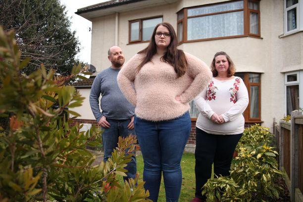 Evie (keskellä) ei halua liikkua julkisesti isäpuolensa ja äitinsä kanssa, koska he ovat kaikki isompikokoisia, kuten Evie asian ilmaisee. Tyttö arastelee muiden tuomitsevia katseita.