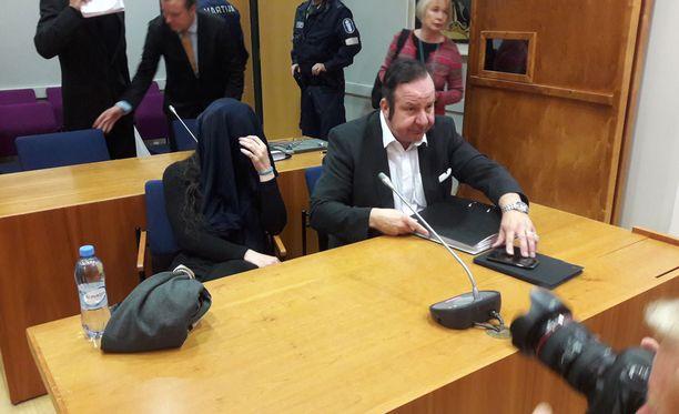 Törkeästä vapaudenriistosta syytetty nainen peitti kasvonsa valokuvaajilta.