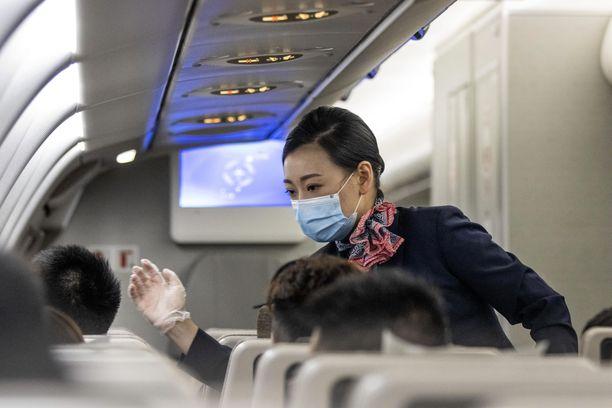 Ulkomaille suuntautuvilla lennoilla kiinalaiselta matkustamohenkilökunnalta vaaditaan paljon laajempaa suojautumista kuin pelkkää kasvomaskia. Kuva otettu 18. kesäkuuta Kiinan sisäisellä lennolla.
