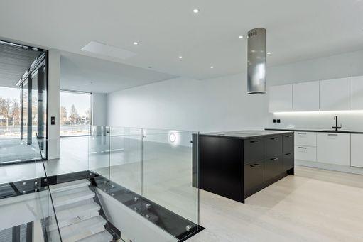 Vaalea puunvärinen lattia, mustavalkoiset kaapistot, saareke ja paljon lasipintaa ja valkoiset seinät.