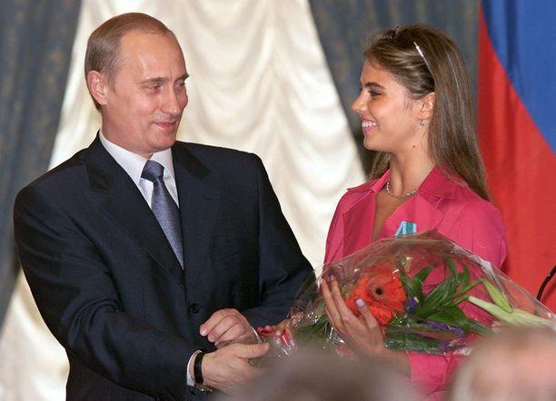 Vladimir Putin on liitetty useisiin julkisuudessa esiintyneisiin naisiin, mutta vahvimmat spekulaatiot koskevat 31-vuotiasta Alina Kabajevaa. Kuvassa Putin ojentaa Kabajevalle kukkia kunniamerkin myöntämisen yhteydessä vuonna 2001.