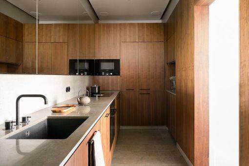 Tähänkin keittiöön peili tuo tilan tuntua. Pähkinäviilukaapistot on toteutettu mittatilaustyönä. Tasot ovat Lagos Blue -marmoria.