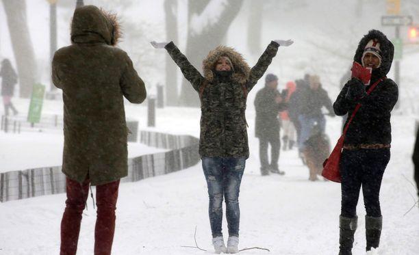 Ihmiset nauttivat lumesta ja ottivat kuvia Central Parkissa New Yorkissa.
