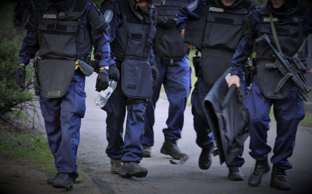 Raskaasti aseistautuneet poliisit tunkeutuivat asuntoon aamuyöllä. Kuvituskuva.
