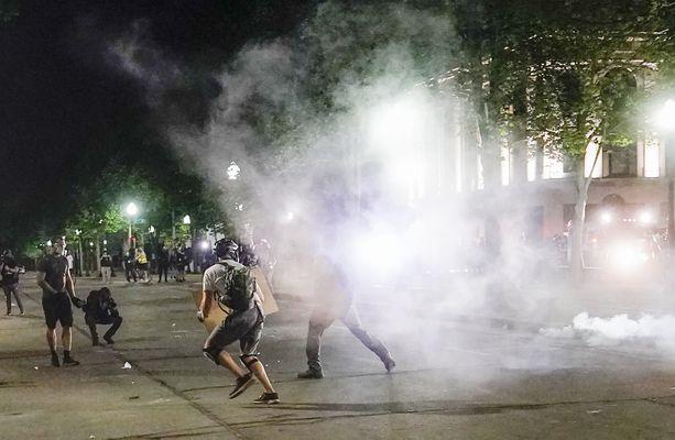 Mielenosoittajat pakenevat poliisin käyttämää kyynelkaasua Kenoshassa maanantaina.