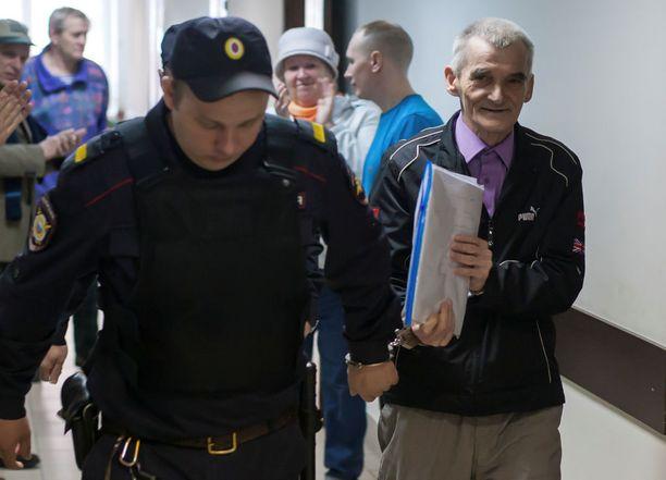 Historiantutkija Juri Dmitrieviä (oikealla) syytetään muun muassa lapsipornorikoksista. Hänen asianajajansa mukaan syytteet ovat tekaistuja. Kuvassa Venäjän poliisi saattamassa Dmitrieviä oikeuden kuulemiseen.