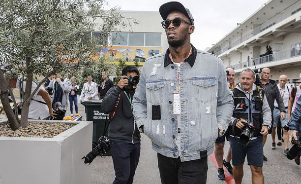 Toimittajat ja kuvaajat seurasiat Usain Boltia Austinin radan varikolla.