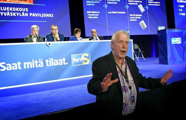 """Perussuomalaisten """"työmies"""" Matti Putkonen joutui häätämään joukon puhujakorokkeen eteen rynnänneitä puoluekokousedustajia voimakkaiden sanojen kera."""