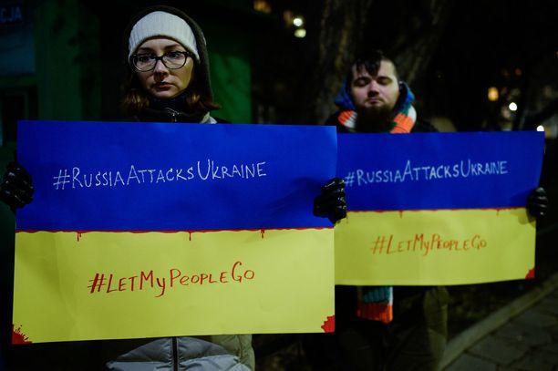 Ihmiset protestoivat Venäjän aggressiota vastaan Venäjän konsulaatin edessä Puolan Krakovassa maanantaina.