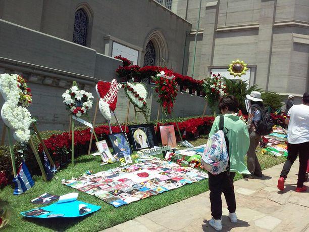 Fanit ovat jättäneet muistoesineitä hautarakennuksen seinää vasten.