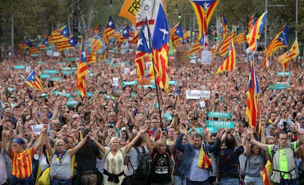 """Mielenosoittajat kantoivat Katalonian lippuja ja banderolleja, joissa luki """"Auttakaa Kataloniaa""""."""
