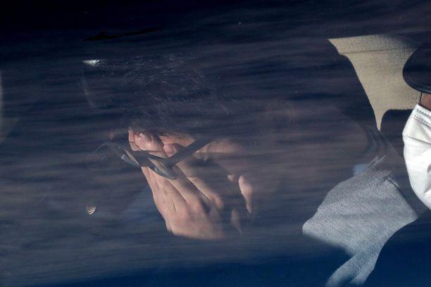 Takahiro Shiraishi peitti kasvonsa istuessaan poliisiautossa Tokiossa Japanissa.