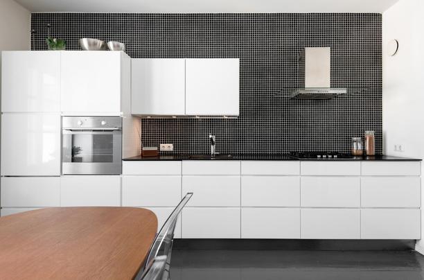Pelkistettyä ja modernia pienellä twistillä. Valkoista keittiötä on piristetty välitilan mustilla mosaiikkilaatoilla.