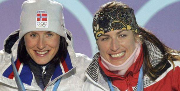 Marit Björgen (vas.) voitti naisten 15 kilometrin yhdistelmäkilpailun. Häntä ryöpyttävä Justyna Kowalczyk (oik.) jäi kolmanneksi.