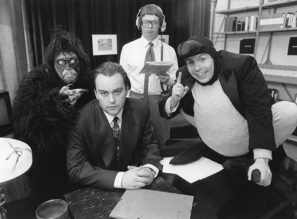 Kyllä lähtee! Ilmaus oli Kummeleista tuttu jo vuonna 1993. Burman simpanssina Heikki Hela, Mauno Ahosena Heikki Silvennoinen, Olli Keskinen edessä ja pöydällä Timo Kahilainen.