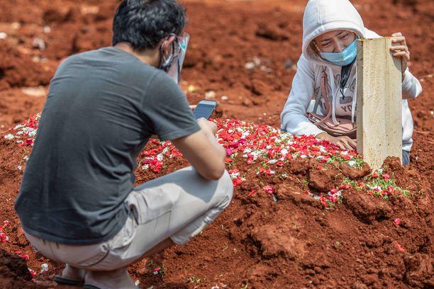 Tiistaina julkaistu luku on maan historian suurin. Nainen suree koronaan kuollutta sukulaistaan Indonesian Etelä-Tangerangissa.