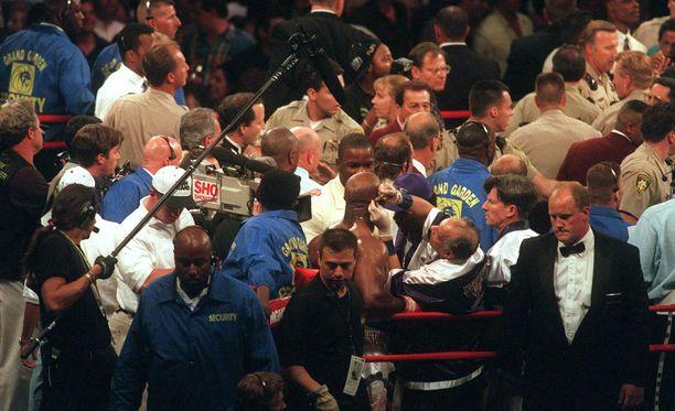 Tysonin pureman jälkeen kehässä oli täysi kalabaliikki. Kuvan keskellä Holyfieldin verenvuotoa tyrehdytetään.