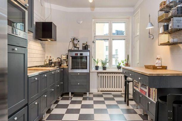 Keittiökaappien tumma sävy toistuu myös lattiassa.