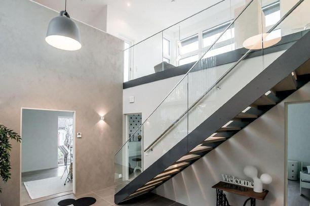 Seinän vierustaa kulkevat teräsportaat sopivat modernin talon tyyliin. Harmonisen tyylin kruunaavat puuaskelmat ja lasikaide,