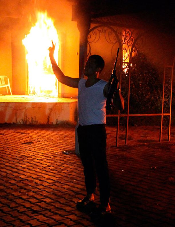 Aseistautunut mies seisoi liekehtivän lähetystön edustalla Libyassa tiistaina.