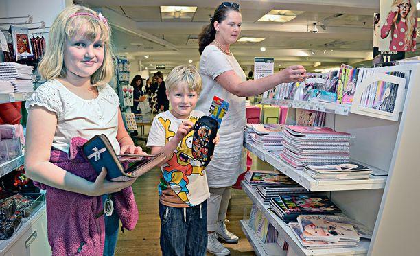Sisarukset Nelli Tamminen, 10, ja 7-vuotias Martti Tamminen olivat koulutarvikeostoksilla perjantaina. Äiti Leena Tamminen päivitteli koulutarvikkeiden korkeita hintoja.