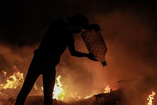 Mies kaatoi vettä palavan barrikadin eteen 29. marraskuuta Baghdadissa väkivaltaisen hallituksen vastaisen mielenosoituksen aikana.