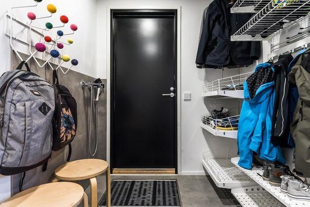 Tässä kodissa on erikseen arkieteinen, joka mahdollistaa sen, että pääsisäänkäynti pysyy siistinä. Arkieteisessä on oma pesupiste, kurasyöppö ja valtavasti tilaa kengille, harrastevälineille ja takeille.