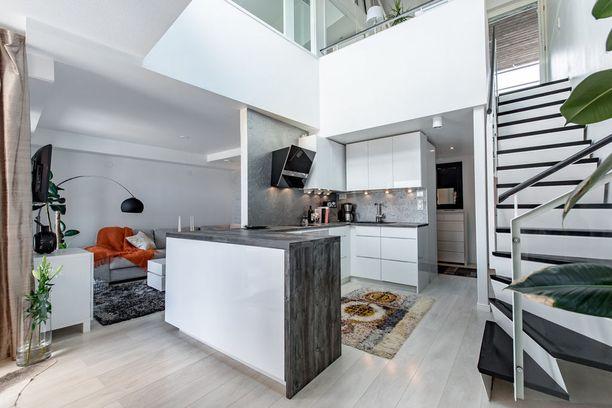 Kun huonekorkeus on hulppea, samaan tilaan saa kaksi kerrosta. Alakerran hieno oivallus on tämä: keittiön voi rakentaa vaikka keskelle huonetta, kun sille tekee oman kulmauksensa.