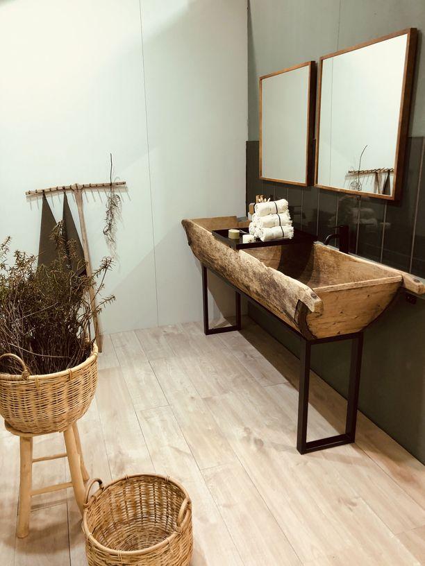 Persoonallisessa kylpyhuoneessa näkyy trendikäs puu, vihreä väri ja rohea rottinki. Omintakeinen pesuallas kiinnittää huomion.