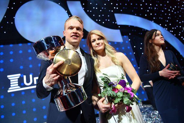 Kolminkertainen vuoden urheilija Iivo Niskanen poseerasi Urheilugaalan lavalla kahden kullan - kiekon ja puolisonsa Saanan - kanssa.