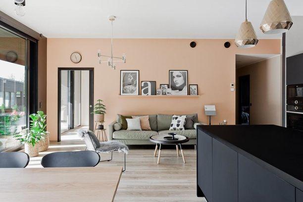 Tässä kodissa olohuoneen trendikäs tunnelma syntyy seinän väristä. Nyt trendikkäitä ovat lämpimät kuparin ja persikan sävyt. Huomaa myös muodikkaat metalliset valaisimet.