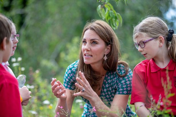 Catherine kumartui lasten tasolle jutellessaan heille.