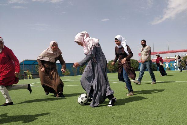 Tytöt nauttivat jalkapallon pelaamisesta.