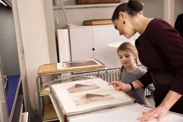 Kuvassa Estelle tutustumassa kirjaston arkistojen kokoelmiin.