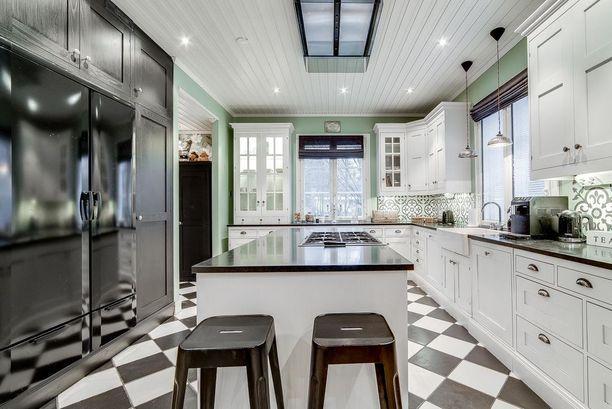 Isosta keittiöstä on helppo luoda toimiva. On tilaa sekä kaapistoille että saarekkeille. Ylellistä tunnelmaa tuovat klassiset ruutulattiat.