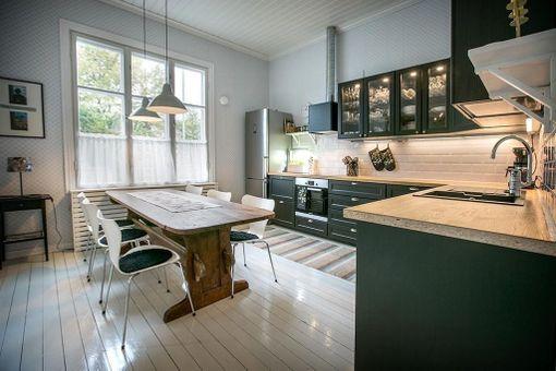 Mikä yhdistelmä! Mustat, trendikkäät keittiönkaapit ja vanhanaikaiset salusiinit ikkunoissa - tämä keittiö todella yhdistää uutta ja vanhaa kotoisalla tavalla.