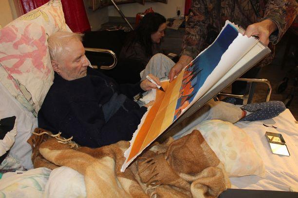 Juhani Palmu signeerasi lauantaina omistajaa vaihtaneen maalauksensa. Taustalla Leila Palmu.