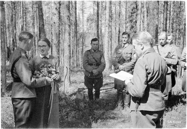 Sotilaspastori Leinonen vihkimässä pariskuntaa kenttähäissä.