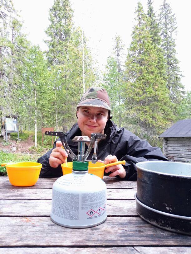 Outi syömässä lounasta Porontimajoen autiotuvan pihamaalla.