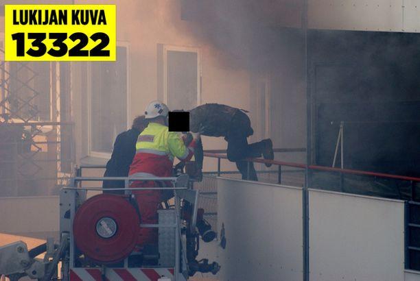 Pelastajat saivat miehen pois palavasta asunnosta nostolava-auton avulla.
