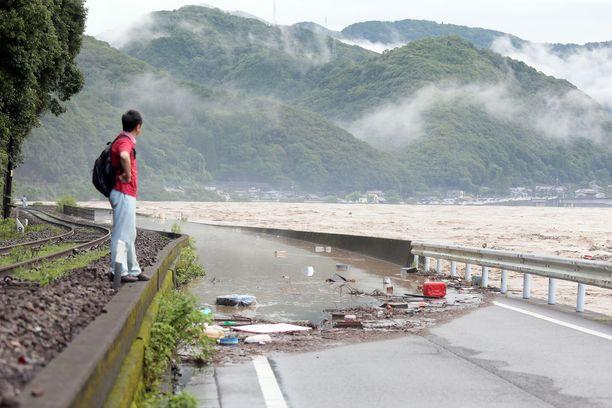 Mies katselee tulvivaa Kuma-jokea Kumamoton prefektuurissa Lounais-Japanissa.