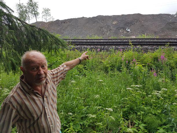 Timo näyttää näkymää talostaan, jonka ohi ajaa Jyväskylään menenvä juna.